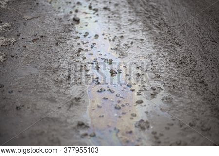 Gasoline Stain On The Pavement. Rainfall After Rain. Multi-colored Stains From Petroleum Products.