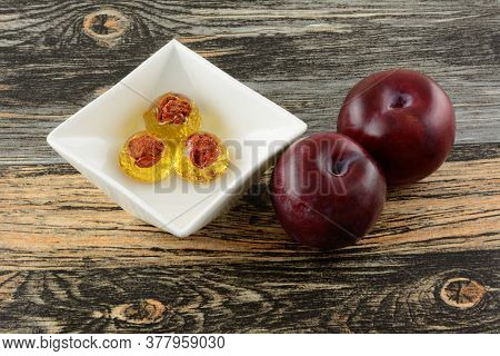 Plum Hard Candy Drops With Plum Pit In Center In White Candy Dish And Fresh Raw Plum Fruit On Table