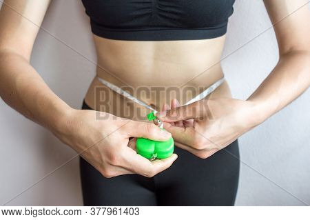 Athletic Slim Woman Measuring Her Waist By Measure Tape. Fit Fitness Girl Measuring Her Waistline Wi