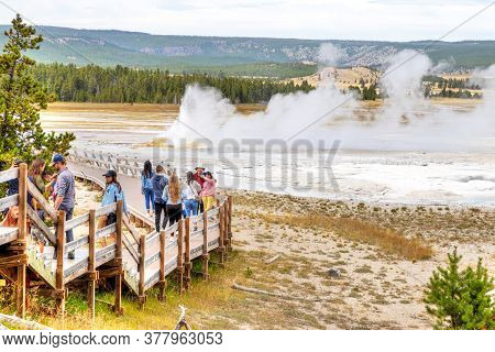Wyoming, Usa - Aug. 24, 2019: Tourists Visit An Erupting Clepsydra Geyser In The Lower Geyser Basin