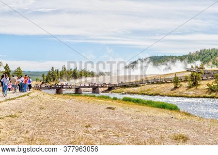 Wyoming, Usa - Aug. 24, 2019: Visitors Approach The Footbridge To Grand Prismatic Spring In Yellowst