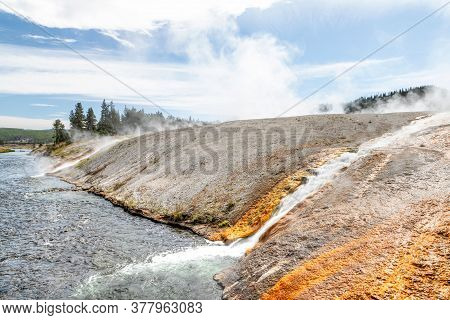 Hot Water Runoff From Excelsior Geyser Flowing Into The Firehole River At Yellowstone National Park'