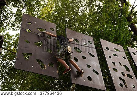 The Guy Goes Through The Obstacle Course On The Rope Park
