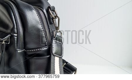 Black Bag On A Light Background. Locks And A Strap On A Womans Bag. An Accessory For A Fashionable L