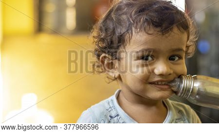 Laughing Baby Chewed With The Teeth Of Nibble A Milk Bottle