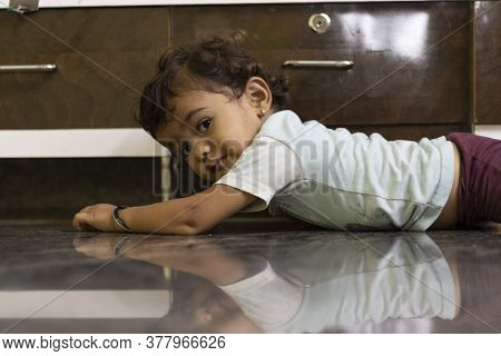 A Little Baby Lying Down And Looking At The Camera, The Image Of A Little Boy Showing On A Transpare