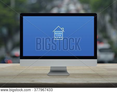 Work From Home Flat Icon On Desktop Modern Computer Monitor Screen On Wooden Table Over Blur Of Rush