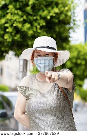 Asian Woman Wearing A Hat And A Surgical Mask Pointing And Looking At The Camera . Lifestyle Concept