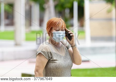 Asian Woman Wearing A Surgical Mask Talking On Her Phone Outdoors . Safety And Communication Concept