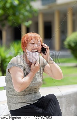 Mature Asian Woman Sitting On A Bench Pulling Down Her Face Mask While Talking On Her Phone.