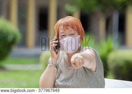 Asian Woman Using A Face Mask Talking On Her Phone While Pointing At The Camera. Communication Conce