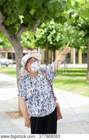 Mature Asian Woman Wearing A Hat And A Face Mask Outdoors Pointing Upwards. Safety And Holiday Conce