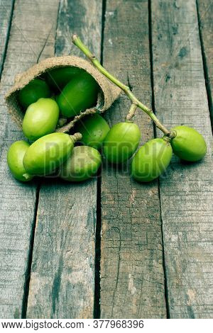 Spondias Mombin  Or Hog Plum In A Jute Sack Isolated On Wooden Background In Vertical Orientation