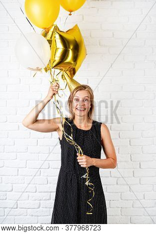 Birthday Party. Young Blond Smiling Woman Wearing Birthday Hat Holding Golden Balloons Celebrating B