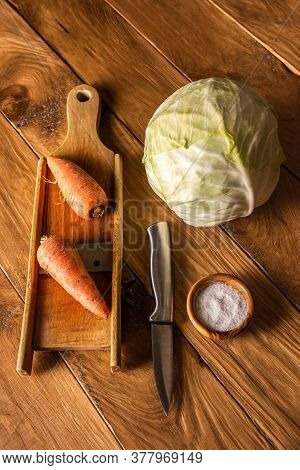 Ingredients Set For Cabbage Fermenting. Metal Knife, Wooden Cabbage Grater, Whole Cabbage, Unpeeled