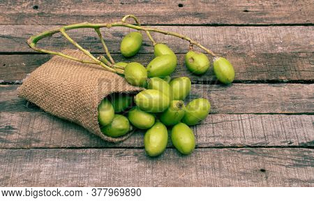 Hog Plum Or Yellow Mombin In A Jute Sack Isolated On Wooden Background
