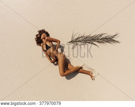Top Aerial Drone View Of Woman In Swimsuit Relaxing And Sunbathing On Beach Near The Ocean. Attracti