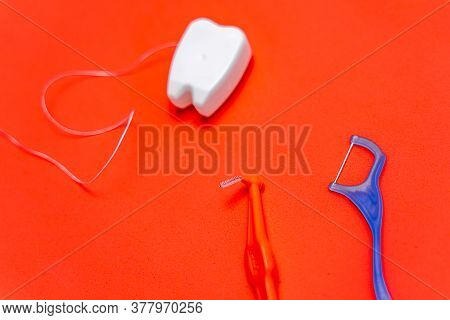 Different Types Of Dental Floss And Tooth Picks On Red Background. Dental Floss In Tooth Toy Shape.