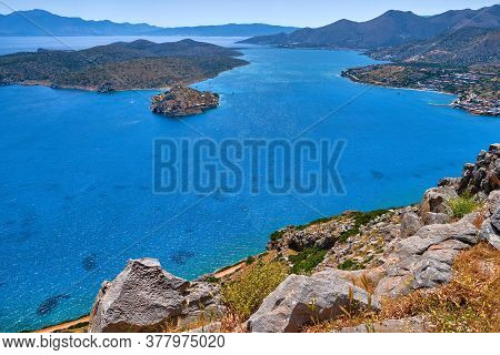 View Of Harbor Between Spinalonga Island And Peninsula, Known As Kalydon, And Plaka Village From Abo