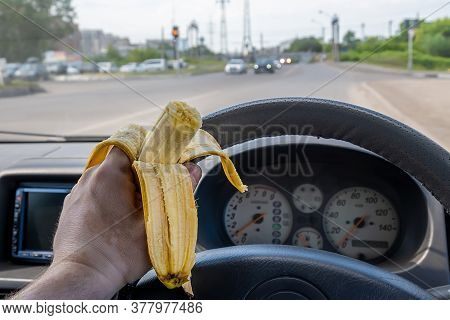 Food, A Banana In The Driver Hand While Driving At The Wheel Of A Car Passing On The Road