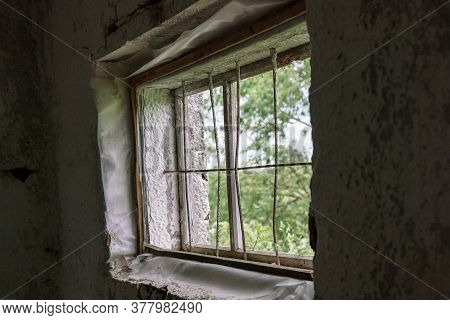 Abandoned Shed Building Window Without Glass Covered With Metal Grid And Dark Premise Walls On Summe