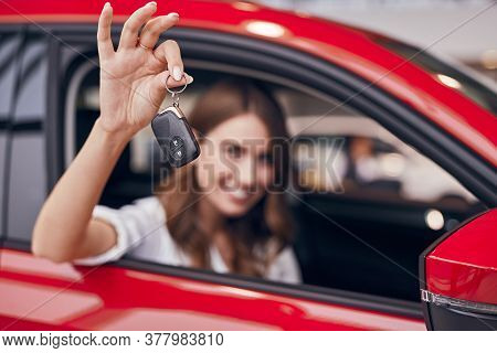 Happy Female Buyer Demonstrating Keys To Camera After Purchasing New Vehicle In Car Dealership