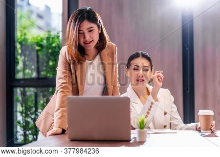 Two Asian Businesswomen Working With The Partner Business Via Technology Laptop In Modern Meeting Ro