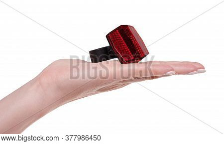 Hand With Red Bicycle Reflector For Safety. Isolated On White Background.