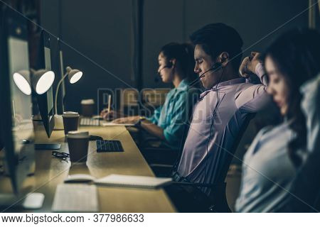 Asian Male Customer Care Service With Business Woman Working Hard Late In Night Shift At Office,call