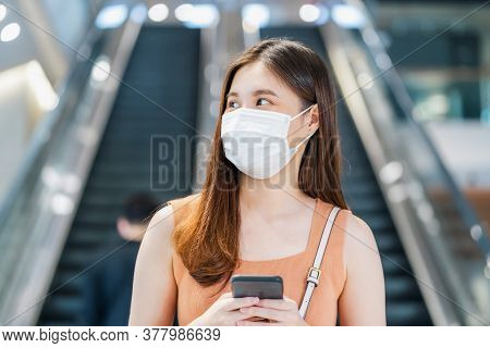 Young Asian Woman Passenger Wearing Surgical Mask And Using Smart Mobile Phone In Front Of Escalator
