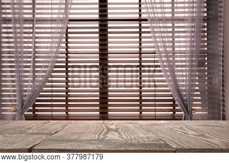 Wooden Table And Window With Blinds On Background