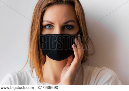 Beautiful Portrait Of A Young Woman In A Black Medical Mask And Blue Eyes And White T-shirt On White