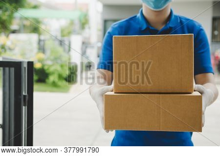 Delivery Service Man In Blue Uniform Waiting For Sending Parcel Post Box To Customer At Door Home, C