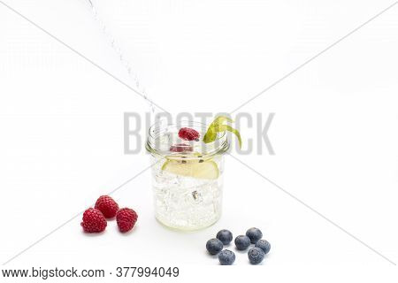 Gin And Tonic In A Glass Jar With Lime, Blueberries And Raspberries. Concept Celebration, Party. Whi