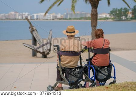 Senior Couple Spending Time Together On The Promenade In The Sunny Day On Blue Sea Background. Aged
