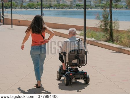 Adult Daughter Accompanies A Disabled Father For A Walk. Adult Children Spend Time With Their Parent