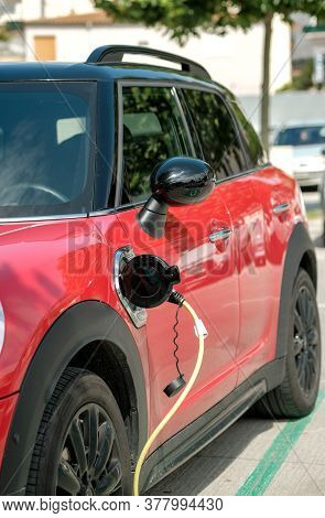Red Electric Car At Charging Station With The Power Cable Supply Plugged On Blurred Background. Powe