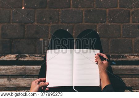 Blank Notebook In Female Hands Together With A Pen, Sitting In A Park On A Bench, Top View. Woman's