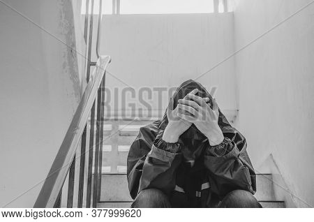 Portrait Of Sad Young Man Covering His Face With Hands Sitting On Old Stairs. Selective Focus On Han