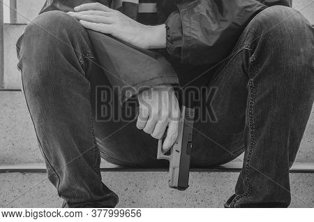 Gangster Men Holding A Gun Sitting On Stairs. Young Men Peaceful Sitting With A Gun On Him Hand Alon