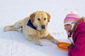 Joyful pretty girl laying with her cute dog in snow on frozen lake poster