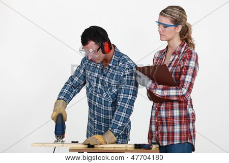 Man using band saw whilst woman supervises