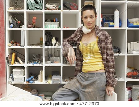 Portrait of young woman leaning on tool shelves