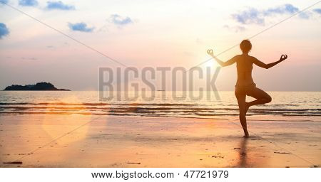 Yoga woman on the beach during sunset (in bright colors)
