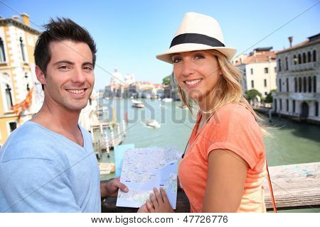 Couplelooking at map on the Academia Bridge in Venice, Italy