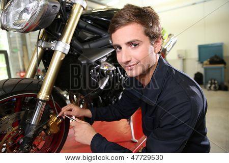 Teenager in professional training, repairing motorbike