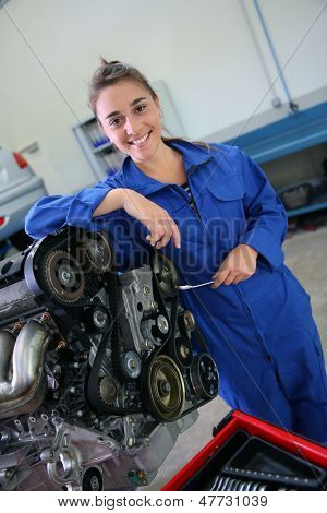 Auto mechanics student girl standing by car engine