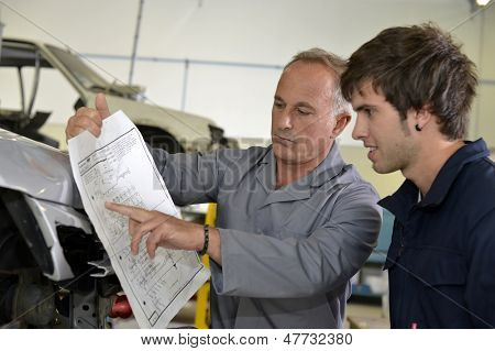 Teacher with coachbuidling student in repairshop