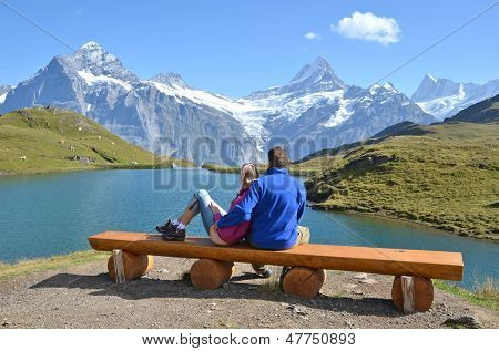 Travelers on a bench enjoying Alpine panorama. Jungfrau region, Switzerland