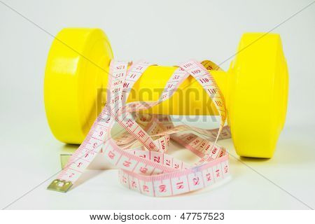 diet concept, dumbbell and measuring tape